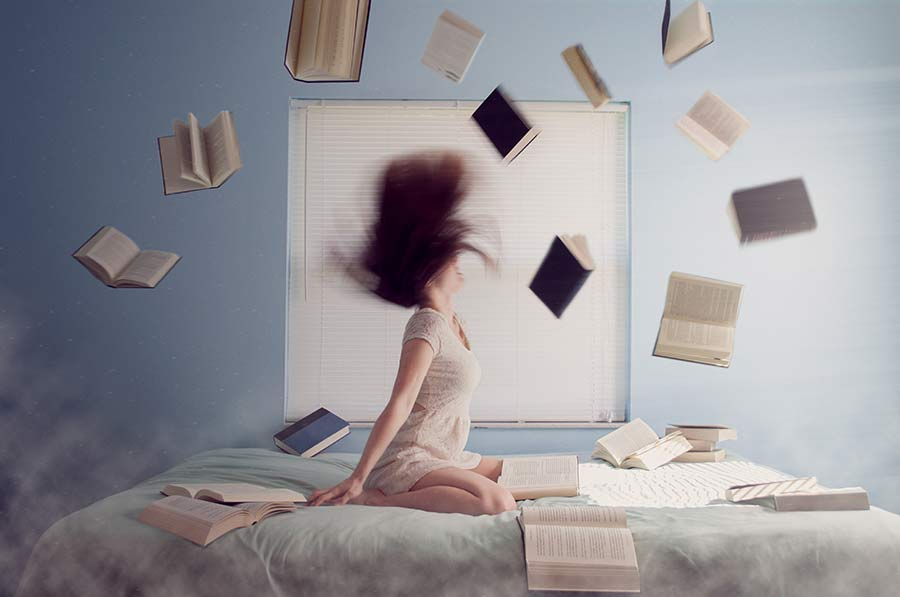 books and woman on bed - addicted to being busy