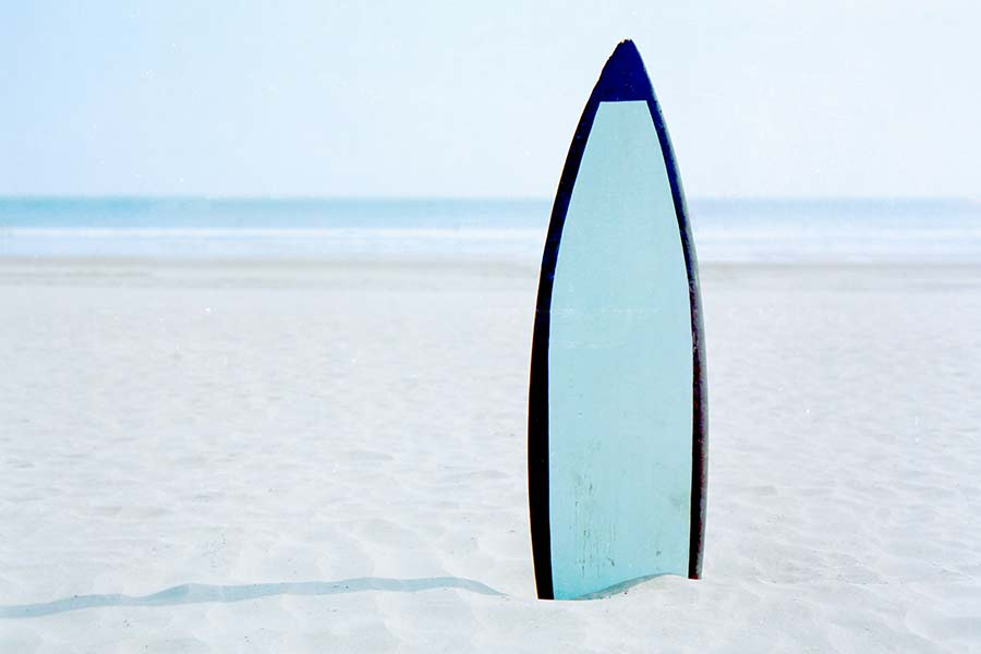 surfboard in sand - beaches beginner surfers